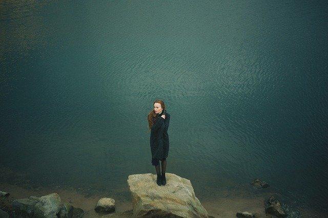 Mulher sobre uma pedra na beira do mar com depressão prestes a se suicidar
